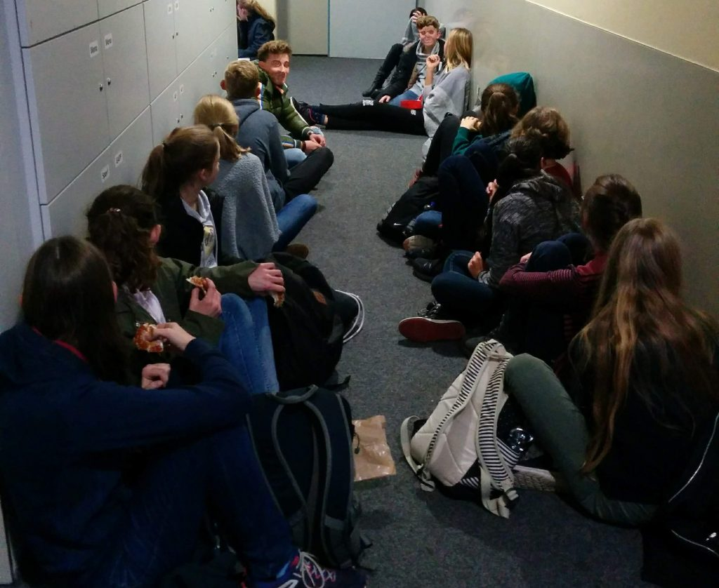 Schüler sitzen auf dem Fußboden
