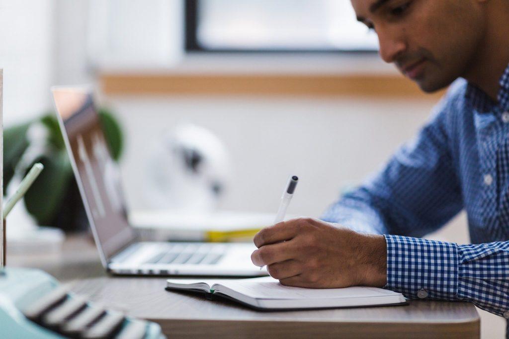 Mann schreibt in ein Notizbuch, mit Laptop
